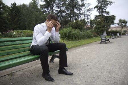 Young businessman sitting on a bench. He has got a bad headache.