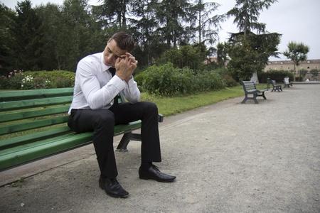 anguished: Giovane imprenditore seduto su una panchina. Sembra che si trova in una depressione totale. Archivio Fotografico