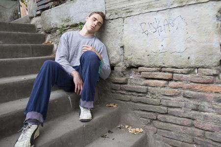 drogadiccion: Retrato de un hombre sin hogar contra una pared.