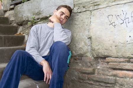 vagabundos: Retrato de un hombre sin hogar con problemas de mal sentado contra una pared. Foto de archivo