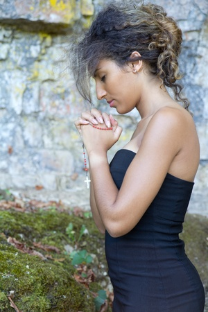 Close-up portrait of a young woman who is praying. She holds a rosary. photo