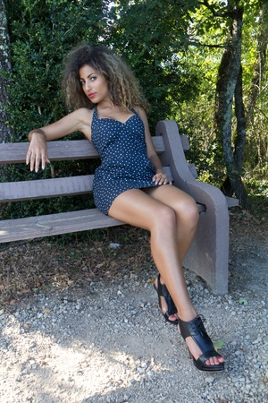 Sexy woman sitting on a bench. She is wearing a short spotted dress.