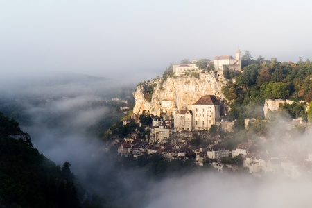 house of worship: Medieval village of Rocamadour by a misty and sunny day. In the middle ages, pilgrims come here and ascend 216 steps on their knees to go to the shrine of Our Lady at the top of the cliff. Stock Photo