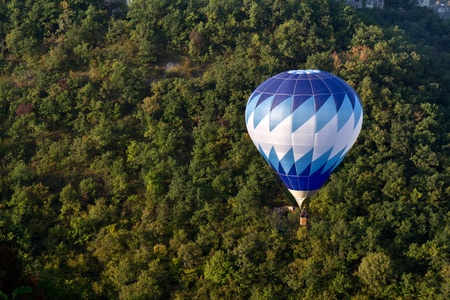 Blue hot air balloon flying near Rocamadour. Stock Photo - 10951402