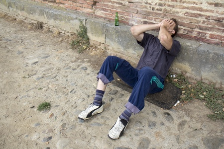 drunkard: Miserable homeless man  is sitting in the street