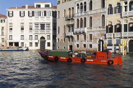 boatman: VENICE, ITALY,- NOVEMBER 25: A barge transporting wholesale goods is sailing on the Grand Canal , on November 25, 2011 in Venice, Italy.