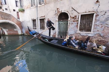 Venice, Italy - November 24, 2011:Gondolier driving a gondola in a narrow canal in Venice (Italy)