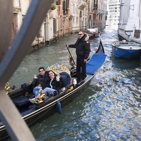 Venice, Italy - November 24, 2011:Gondola with a happy couple in a narrow canal in Venice (Italy).