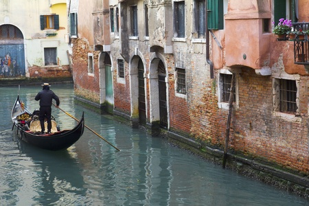 Venice, Italy - November 22, 2011:Gondola in a narrow canal in Venice (Italy)