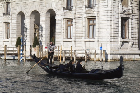 Venice, Italy - November 24, 2011:Gondolier driving a gondola with passengers in the middle of the Grand Canal, in Venice (Italy).