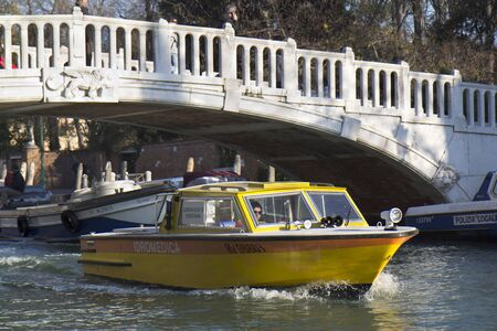 Venice, Italy - November 24, 2011: Yellow medical boat under a bridge of a small canal . Stock Photo - 11652061