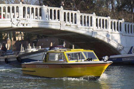 Venice, Italy - November 24, 2011: Yellow medical boat under a bridge of a small canal . Stock Photo - 11652061