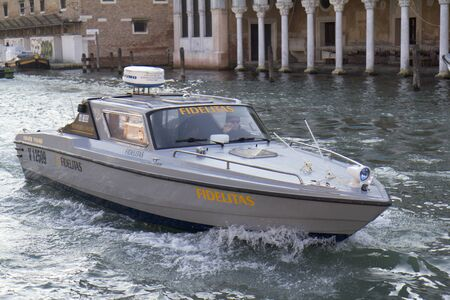 Venice, Italy - November 25, 2011: A speedboat is transfering funds on the grand Canal.