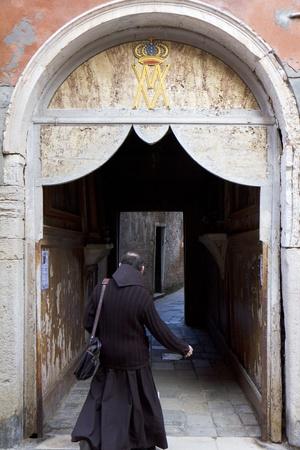 sotana: Venecia, Italia - 22 de noviembre de 2011: el hombre del clero caminar debajo de una puerta con una inscripción religiosa, en la ciudad vieja. Editorial