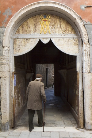 Venice, Italy - November 22, 2011: Old man walking under a door with a religious inscription, in the old city.