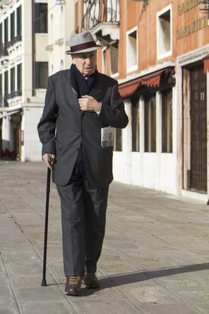 senioren wandelen: Venetië, Italië - 26 november 2011: Classy oude man komt terug van het kopen van een krant in de oude stad.