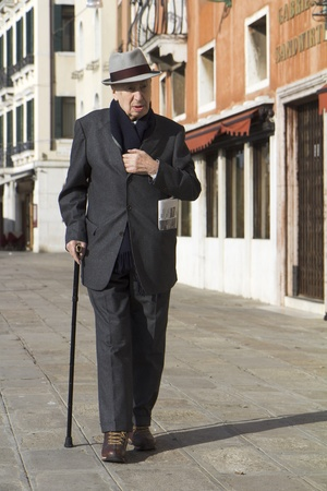 Venice, Italy - November 26, 2011:  Classy old man coming back from buying a newspaper in the old city. Editorial