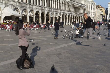 Venice, Italy - November 22, 2011: Two tourists are having fun with the pigeons of the St Mark Square. A woman is taking a photo while his boy friend is jumping up. In the background some other tourists.