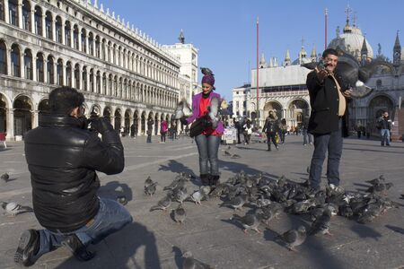 Venice, Italy - November 22, 2011: Tourists are having fun with the pigeons of the St Mark Square. A man is taking a photo. The birds are on their arms, hands, head and at their feet. In the background some other tourists.