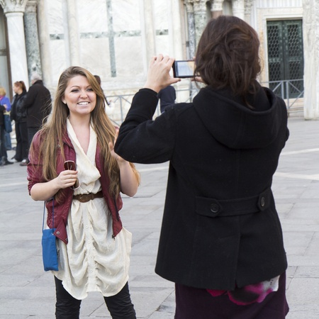 Venice, Italy - November 26, 2011: A young woman is taking a photo of her smiling friend, San Marco square.