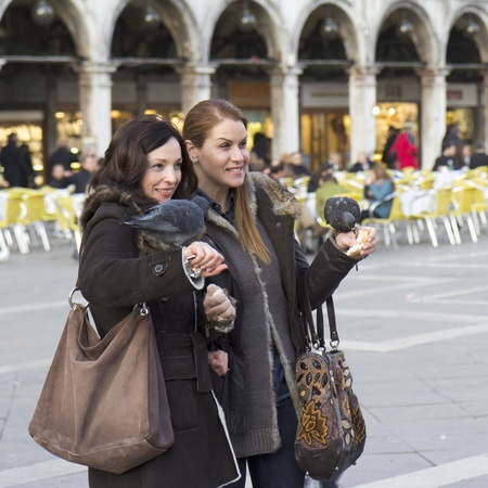 Venice, Italy - November 26, 2011: Two young women are having fun with the pigeons of the St Mark Square. They are standing with the birds on their arms . They are waiting for the photograph.