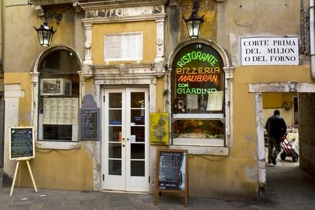 restaurante italiano: Venecia, Italia - 22 de noviembre de 2011: fachada de color amarillo de un restaurante t�pico de la ciudad vieja. A la derecha, un hombre de entrega est� trabajando con su carro.