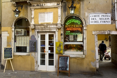 Venice, Italy - November 22, 2011: Yellow facade of a typical restaurant in the old city. On the right, a delivery man is working with his dolly.