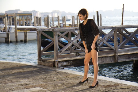 VENICE, ITALY - NOVEMBER 27: An unidentified female fashion model is posing during a public  photography session on the Riva Degli Schiavone near the lagoon , on November 27, 2011, in Venice, Italy.