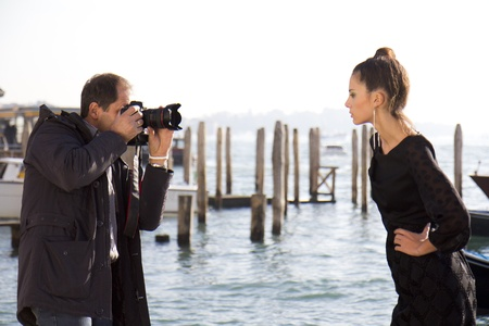 VENICE, ITALY - NOVEMBER 27:  An unidentified photographer take pictures of a female model on the Riva degli Schiavone between the Doges Palace and the lagoon, on November 27, 2011, in Venice, Italy.