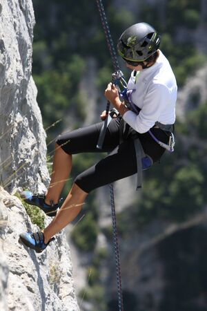 Gorges du Verdon, France - July 25, 2011: Descent of a young female rock climber in a steep cliff.