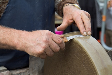 Two hands are holding a blade against a grindstone in motion. Stock Photo