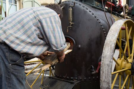 bygone: Seissan, France - August 5, 2011: Logs are put in a steam machine boiler at Lou marcat de beth tems a, a  french traditional market.  Every year, all the town relives the bygone for one day.