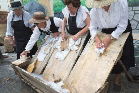 Seissan, France - August 5, 2011: Washerwomen are working at Lou marcat de beth tems a, a  french traditional market.  They use typical old utensils as wooden washboards, beetles and bar of soap. They wear lacy blouse and straw hat.