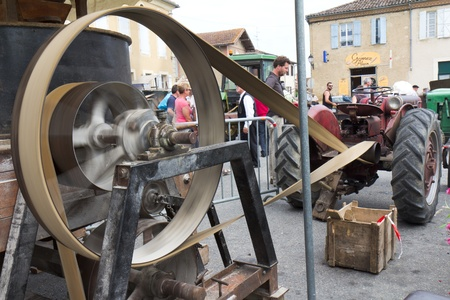 bygone: Seissan,  France - August 5, 2011: Big agricultural machine belt in motion at Lou marcat de beth tems a, a  french traditional market.  Every year, all the town relives the bygone for one day.