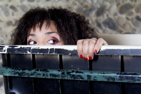 A woman is peering out of a trash container. She is worried. Stock Photo