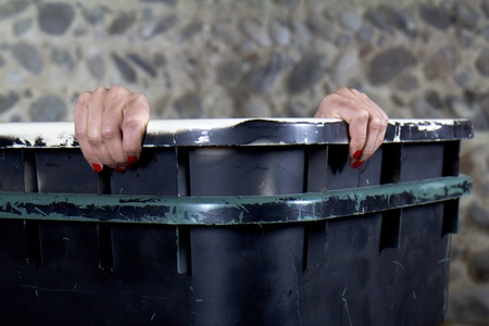 A woman is going to peek out of a garbage container. Stock Photo - 12085165