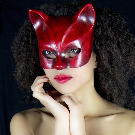 Sensual and attractive woman wearing a red venetian mask. She is posing in front of a black background.