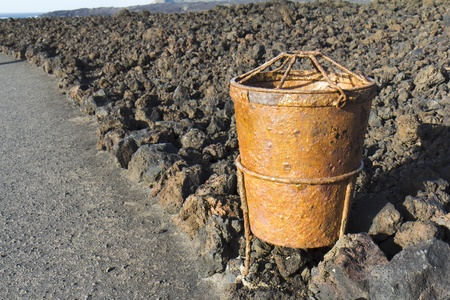 There is a rusty trash can on the edge of a lava field, Lanzarote, Canary Islands, Spain  photo