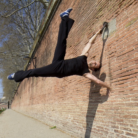 A man is hanged at a ring in an acrobatic position  He is working along a wall of red bricks  Stock Photo