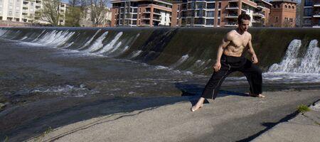 buena postura: Un hombre musculoso es ejercicio al aire libre en un d�a soleado Foto de archivo