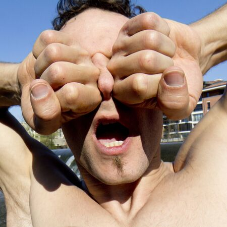 A man puts two fists on his eyes. He does not see anything. His nose is deformed. photo