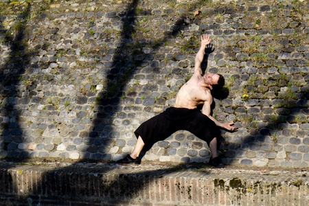 A dancer, shirtless,  moves along a stone wall between the shadows of branches and trunks. Stock Photo - 13330794
