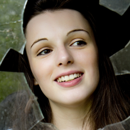 Portrait of a young woman who is smiling behind a broken window  photo