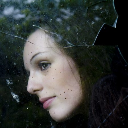 Close-up portrait of a pensive young woman who is behind a stained and broken window  photo