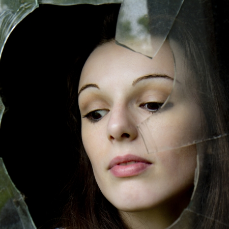 Close-up portrait of a pensive woman who is behind a dirty and broken window  photo