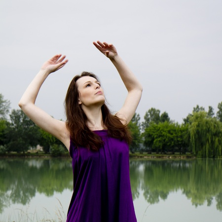A woman wearing a purple dress is raising her arms near a lake  photo