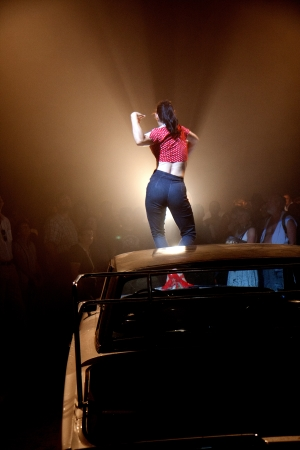 big top: AURILLAC, FRANCE - AUGUST 22: a woman dances and sings on the bonnet of a car under a big top, Aurillac International Street Theater Festival, Company Off ,on august 22, 2012, in Aurillac,France. Editorial
