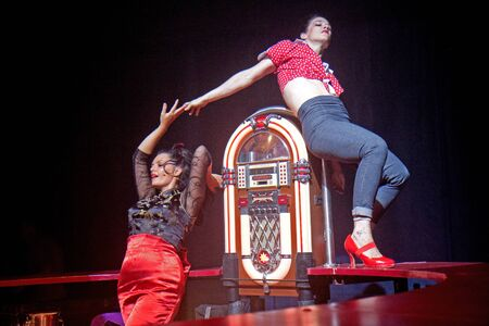 AURILLAC, FRANCE - AUGUST 22: two women dance on a bar under a big top as part of the Aurillac International Street Theater Festival,show by the Company Off ,on august 22, 2012, in Aurillac,France.