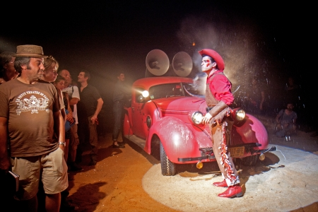 cantal: AURILLAC, FRANCE - AUGUST 22: a cowboy arrives in a red car under a big top as part of the Aurillac International Street Theater Festival, Company Off ,on august 22, 2012, in Aurillac,France.