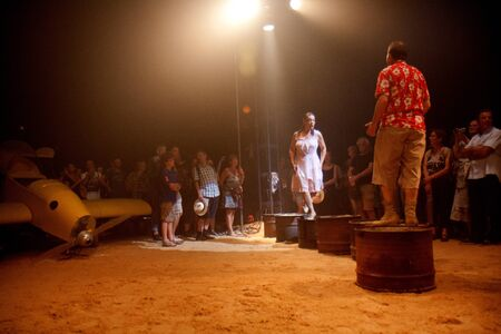 big top: AURILLAC, FRANCE - AUGUST 22: a couple is walking on petrol cans in the middle of a big top, Aurillac International Street Theater Festival, Company Off ,on august 22, 2012,in Aurillac,France. Editorial